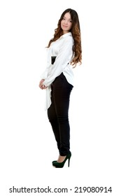 Beautiful sexy brunette girl in a white blouse and black trousers, posing on a white background isolated