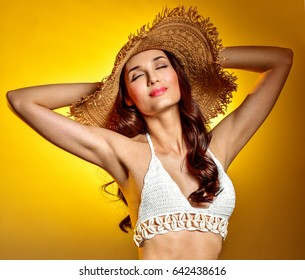 Beautiful sexy brunette  in hat and bikini on a yellow background. Armpit's care. Armpit epilation, hair removal, perfect skin.