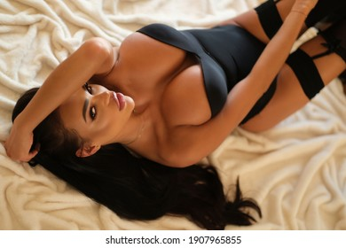 Beautiful and sexy brunette is lying on the blanket.