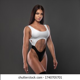 Beautiful sexy brunette in a sports bikini on a gray background.