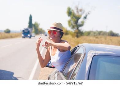 Beautiful sexy brunette woman, has happy fun smile face, sunglasses, hat. Urban city portrait. Attentive driver car. Close up