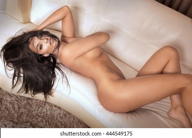 Beautiful sexy brunette woman lying naked on couch, looking at camera. Perfect slim body. Indoor photo.