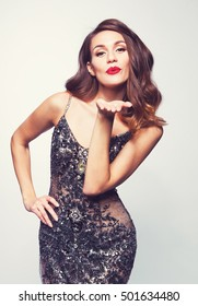 Beautiful sexy brunette woman on grey  background, in sparkly dress  party.