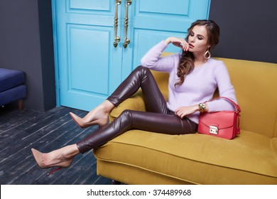 Beautiful sexy brunette woman sitting on a couch, wearing a stylish fashionable tight pants eco leather cashmere sweater, clothing catalog, red bag, room interior, door