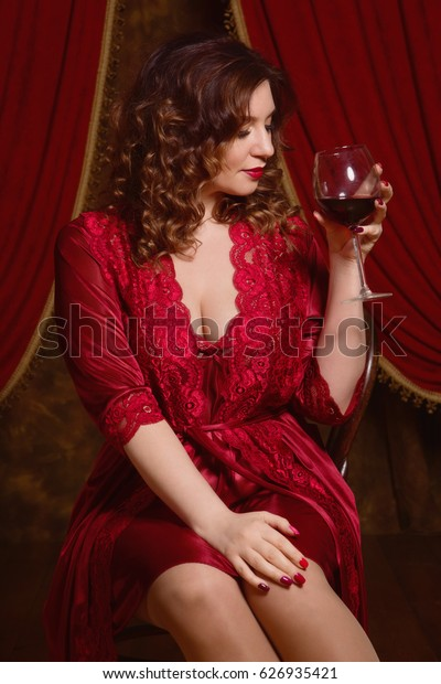 Beautiful and sexy brunette woman wearing red lingerie with a glass of wine