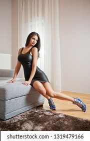 Beautiful sexy brunette young woman wearing black leather short dress sitting on bed. Fashionable female with attractive body posing provocatively, indoor. Sensual girl on blue sandals with high heels