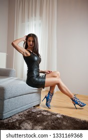 cb320bed6cb Beautiful sexy brunette young woman wearing black leather short dress  sitting on bed. Fashionable female