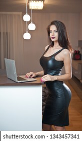 Beautiful sexy brunette young woman with black leather sexy short dress and a laptop. Fashionable female with attractive body posing provocatively, indoor. Sensual girl with laptop looking forward