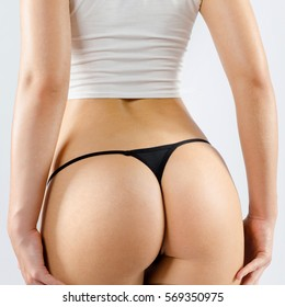 Beautiful sexy butt in thongs of young girl isolated on gray background.