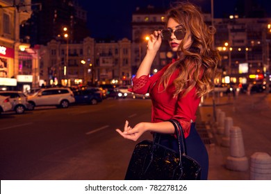 Beautiful sexy caucasian woman with long curly brunette hair and make up on big eyes and full sensual lips. She coming back from party, walking in office dress on european street with traffic lights