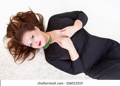beautiful sexy chubby girl lies on a white background in a black dress large