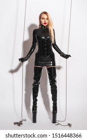 Beautiful sexy dominant vamp mistress dominatrix bdsm doll face blonde woman fashion model in glamour black latex dress, underbust corset, sex shop style, and fetish patent leather knee-high boots