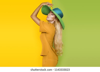 Beautiful, sexy, elegant woman with blond hair poses in studio in elegant yellow clothing and hat.
