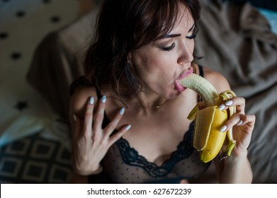 beautiful sexy erotic brunette sucking and eating a banana