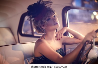 beautiful sexy fashion blond girl model with bright makeup and curly hairstyle in retro style sitting in old car