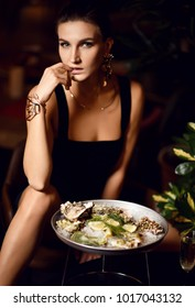 Beautiful sexy fashion brunette woman in expensive interior restaurant eat oysters and waiting on dark cafe background