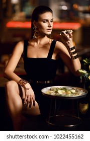 Beautiful sexy fashion brunette woman in expensive interior restaurant eat oyster and lick one finger on dark cafe background