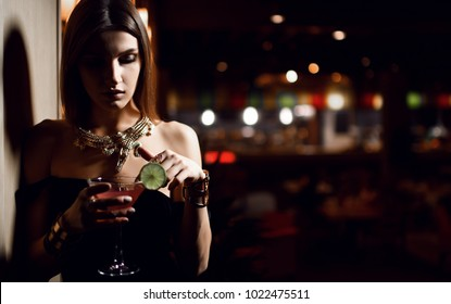 Beautiful sexy fashion brunette woman in expensive interior restaurant relaxing with martini cosmopolitan cocktail in big chair on dark cafe background