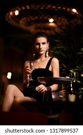 Beautiful sexy fashion brunette woman in bar restaurant relaxing drinking champagne wine on dark cafe background