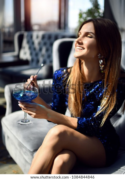 Beautiful sexy fashion brunette woman in expensive interior restaurant drinking drinking blue margarita sparkle cocktail
