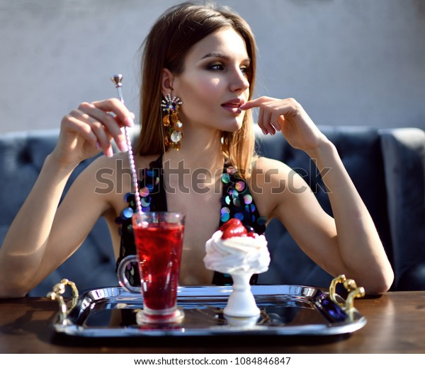 Beautiful sexy fashion brunette woman in expensive interior restaurant drinking drinking red margarita cocktail and eat dessert cake with strawberry