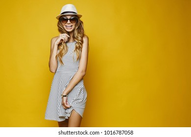 Beautiful, sexy, fashionable blonde girl in white dress, hat and sunglasses posing at yellow background