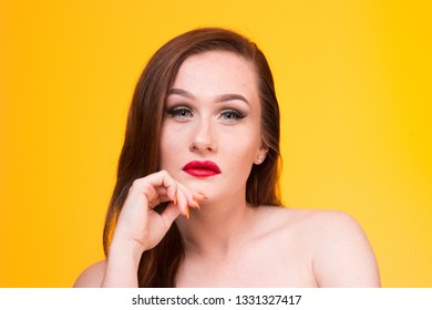 beautiful sexy female brunette model with red lips on yellow background. smokey sultry look