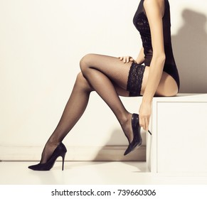 Beautiful and sexy female legs. Fit and seductive woman in nylon stockings.