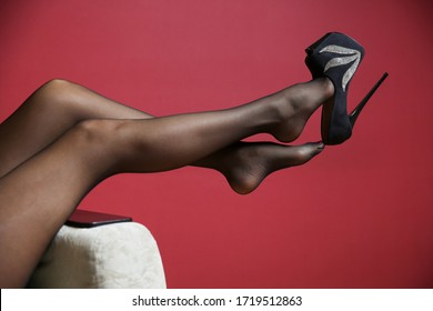 beautiful sexy female legs in high heel shoe on red background close up