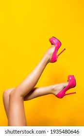 Beautiful Sexy Female legs wearing pink high heels over yellow background