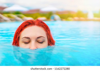 Beautiful sexy female relaxing In swimming pool water. Girl with healthy tanned skin, gorgeous face and enjoying sun on hot summer day. Half head above water stalking. Relax concept with copy space