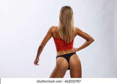 Beautiful sexy fitness girl shows muscles on white background