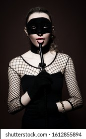Beautiful sexy girl in a black dress blonde, mask stack in the hands posing on a brown background