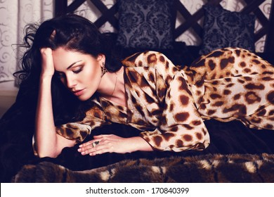 beautiful sexy girl with black hair lying on sofa