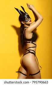 Beautiful sexy girl in a black leather mask and harness on a yellow background in studio