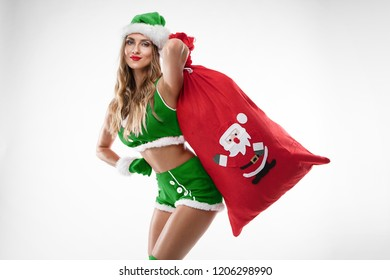 beautiful sexy girl with gifts bag wearing santa claus clothes over white background