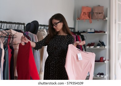 beautiful sexy girl in glasses in store choosing what dress to buy and wear. difficult choice