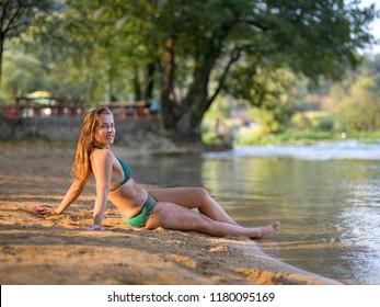 a beautiful sexy girl in a green bikini relaxing and enjoying in nature on the riverbank