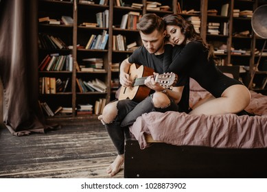beautiful sexy girl and her boyfriend playing guitar.