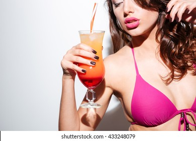 Beautiful sexy girl holding cocktail wearing bikini isolated on the white background