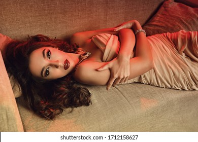 Beautiful sexy girl in a light dress lies on a sofa