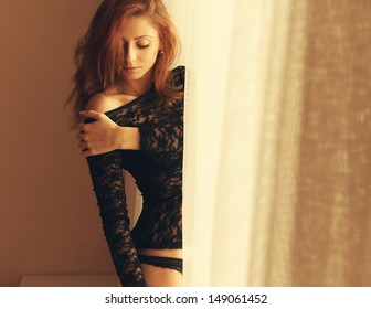 Beautiful sexy girl in lingerie at home on a sunny day near the window