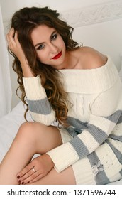 A beautiful sexy girl with long hair in a knitted sweater is smiling and sits on a white bed