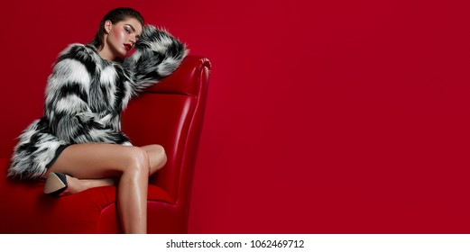 A beautiful, sexy girl with long legs in high-heeled shoes sits in a black and white fur coat on a red armchair in the studio on a red background.