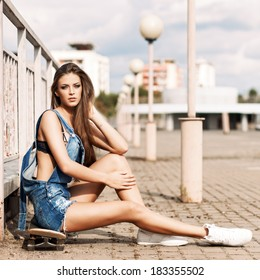 beautiful sexy girl with long legs in jeans short overalls sits on skateboard near fence setting her long silky hair
