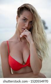 Ein schönes sexy Girl Model entspannt sich am weißen Sandstrand, im roten Bikini-Badeanzug, mit gerbtem Körper, langen blonden Haaren, prächtigen Brüsten und puffigen Lippen. Gesunde Natur, Meereswellen, Wolken auf Bali