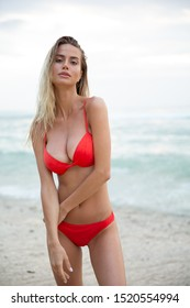 A beautiful sexy girl model relax on white sand beach, in red bikini swimsuit, with a tanned body, long blonde hair, magnificent breasts and puffy lips. Healthy nature, ocean waves, clouds on Bali