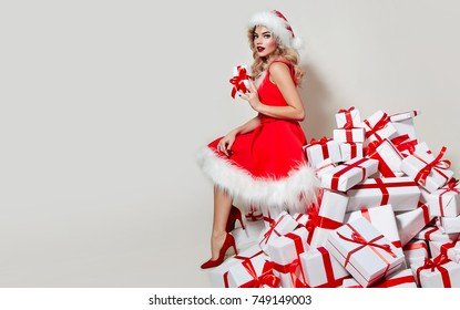 Beautiful sexy girl in a New Year's dress lying on a mountain of gifts.New Year, Christmas, holidays, souvenirs, gifts, shopping, discounts, shops, Snow Maiden Santa Claus,make-up, hairstyle,carnival.