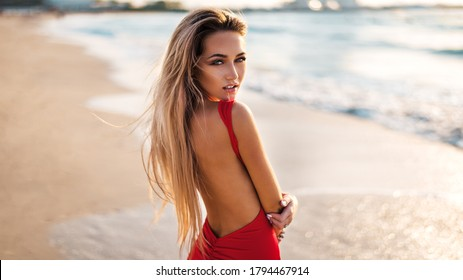 Beautiful sexy girl on the sea beach in a red dress looks at the camera hair fluttering wind at sunset. Close-up of a fashionable naked girl in a swimsuit. Close-up fashion portrait of model outdoor