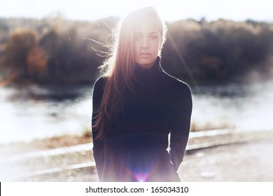 Beautiful sexy girl on the street against the sun